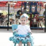 little girl with zebra tutu sitting in teal rocking chair