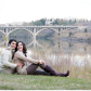 couple sits in front of the bridge